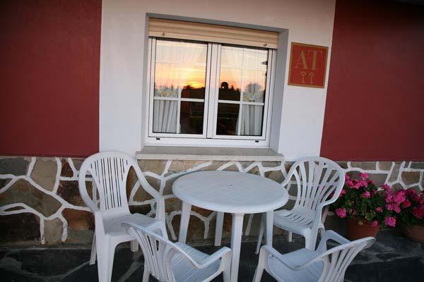 Vistas de unas sillas y mesa en el exterior de la casa